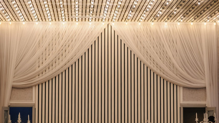 close up photo of a white ceiling and a part of presidium decorated with tulle and lights in a wedding banquet hall