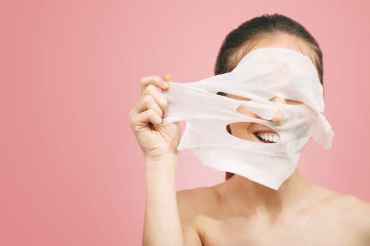 Portrait of beautiful smiling girl removing white sheet mask from healthy fresh skin