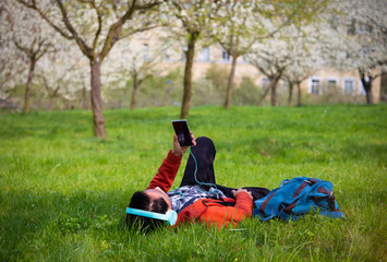 Happy time of young man listening music by headphone and looking his smartphone in the green field garden