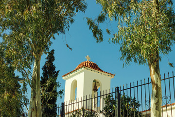 Little beautiful Greek church in blue and white colors on a sunny day against the blue sky on the island of Salamis, Greece.