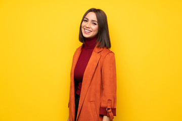 Young woman with coat smiling Wall mural