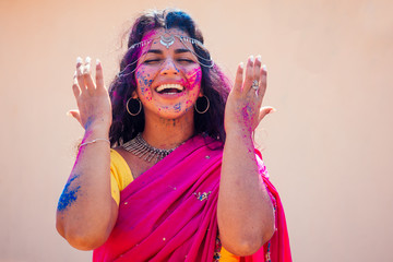 Holi Festival Of Colours. Portrait of happy indian girl in traditional hindu sari on holi color . india woman silver jewelry with powder paint on dress ,colorful pink and blue hair in Goa Kerala Wall mural