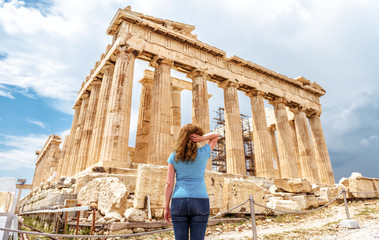 Young woman looks at Ancient Greek Parthenon on the Acropolis of Athens, Greece