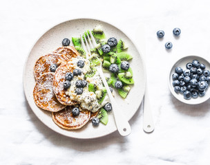 Gluten free pancakes with coconut yogurt, kiwi and blueberries on a light background, top view