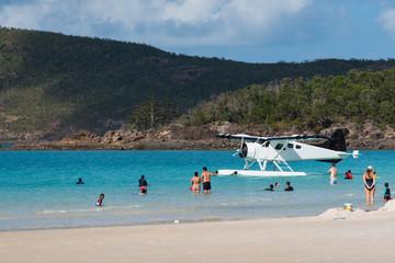 Strand mit Touristen und Wasserflugzeug