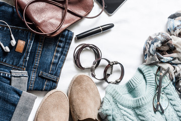 Women's spring clothing set - jeans, suede sneakers, pullover, scarf and leather bag. Women's clothes for spring walks on a light background, top view. Flat lay, copy space