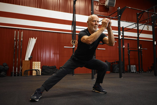 Attractive self determined elderly male with gray hair and beard holding hands in front of him while doing side lunges in gym, having serious concentrated facial expression, dressed in sportswear