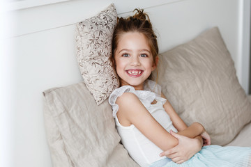 little cute girl is lying on the bed