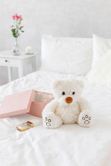 Teddy bear, pink gift box with garland lights and perfume lying on the bed with white linen. Bedside table, vase with rose flowers.  Light female modern stylish and cozy bedroom. Bedroom interior.