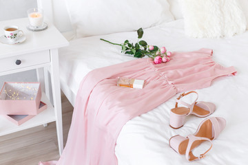 Elegant long pink dress, heeled sandals, perfume and rose flowers lying on the bed with white linen. Girl choosing outfit. White female modern stylish bedroom.