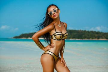 Fashion outdoor photo gorgeous sexy woman in a luxurious gold bikini, perfect dark tanned skin. Tropical island trip