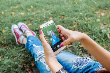 Hipster girl using her smartphone. Young successful woman sitting on social networks and read messages. Girl takes a picture of their sneakers on a mobile phone.