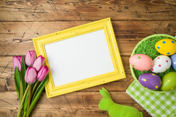 Easter holiday background with photo frame; easter eggs in basket and tulip flowers on wooden table.