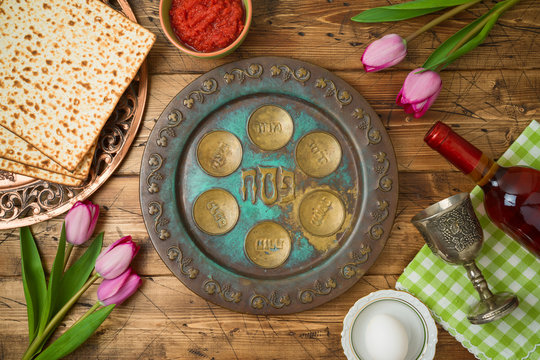 Jewish holiday Passover background with matzo, seder plate, wine and tulip flowers on wooden table.