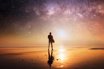 A concept picture of man holding a surfboard, silhouetted against the setting sun with stars and the universe overhead at night.
