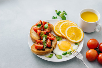 Breakfast of eggs and sandwiches with tomatoes and orange juice close up