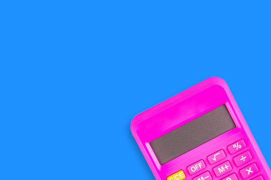 One digital pink plastic calculator on blue table in office. Copy space for your text. Top view. Financial or education concept