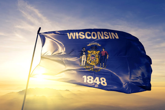 Wisconsin state of United States flag waving on the top sunrise mist fog