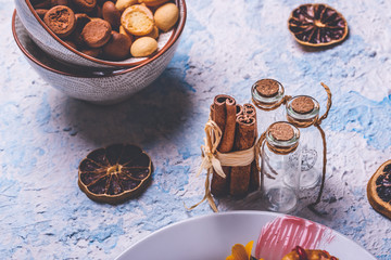 Few cinnamon sticks and small glass bottles on light wooden board