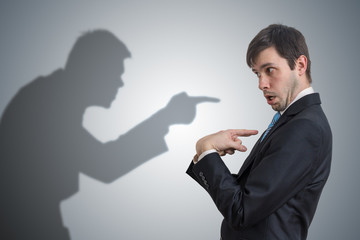 Shadow of man is pointing and blaming businessman. Conscience concept.