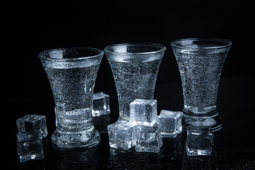 Russian vodka shot with ice on black background