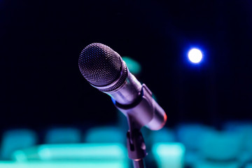 Wireless microphone on stand on blurred background. Empty audience.