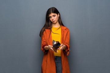 Teenager girl with coat over grey wall holding a wallet