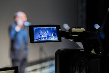 Video shooting of the event. Camcorder with LCD display. 2 men on stage in front of microphones on a gray screen background.