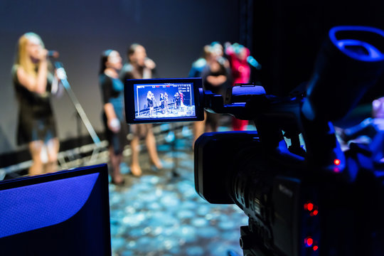 Video recording of the concert. Girls sing in microphones. Camcorder with LCD display. Shooting in the interior, Studio or on stage.