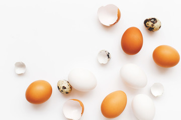 White and brown chicken eggs, quail eggs and broken eggs on white background. Top view. Minimal easter concept.