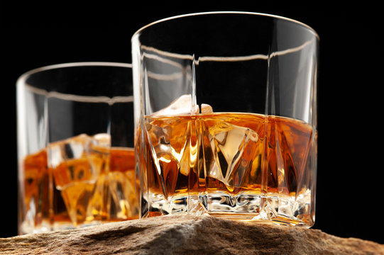 Glass of scottish whiskey with ice cubes