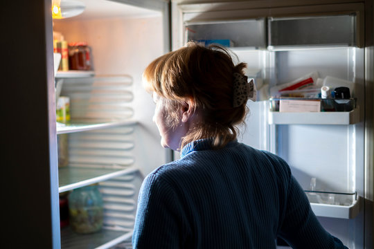 woman by the open refrigerator at night