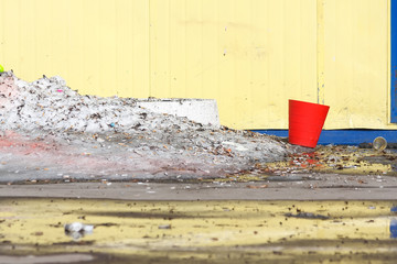 Red plastic bucket against a yellow wall with blue details, next to cigarette butts and a snowdrift of dirty snow.