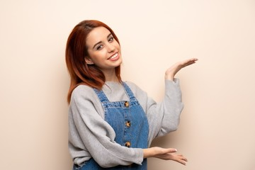 Young redhead woman over isolated background extending hands to the side for inviting to come
