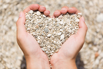 Young female hands hold small pebble stones in heart shape.