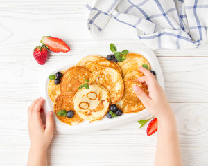 Hands of a small child to reach for pancakes with a smile. Maslennitsa, pancakes with berries on a white background