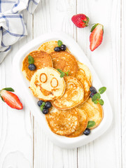 Pancakes with berries on a white plate, with smiles