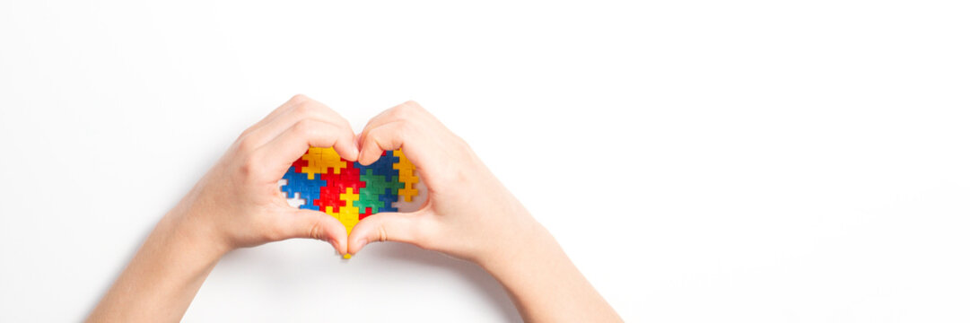 Kid hands in the shape of heart and colorful heart made of plastic construction puzzle pieces on white background. World autism awareness day concept
