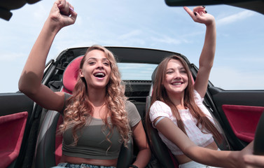 two young women sitting in the front seat of a convertible
