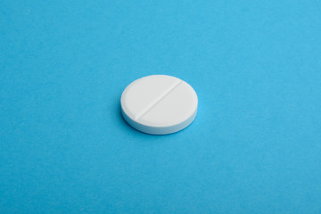 One tablet. Pill isolated on blue background. Copy space for text.