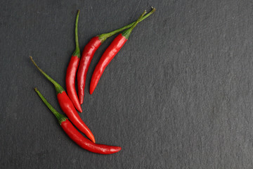 Canvas Prints Hot chili peppers Group of hot spice red chilli fresh cayenne pepper on a black graphite slate stone surface. Natural vegeterian diet organic vegetable. Dark food foto
