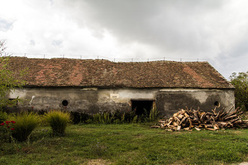 Old farmhouse with pile of wood, wet grass and cloudy sky