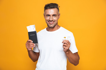 Image of smiling man 30s in white t-shirt holding credit card and travel tickets