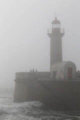 Lighthouse in the fog in stormy weather