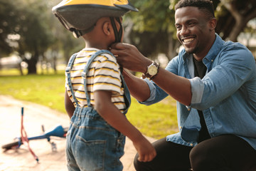 Man helping son wearing helmet for cycling at park