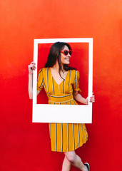 Wall Mural - Beautiful woman posing with empty picture frame