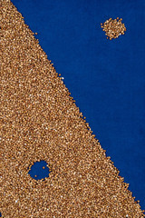 Buckwheat on blue cloth with scattered grains and hole