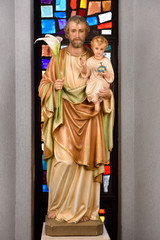 Statue of Saint Joseph foster father holding infant son Jesus and lilies at stained glass window in Saint Roch's Catholic church Toronto Canada