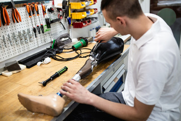 Disabled man working in amputee shop for production prosthetic extremity parts.