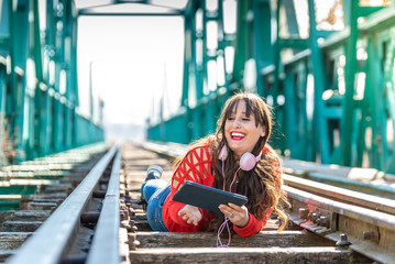 Beautiful Young Woman Lying Down on Train Tracks Using Digital Tablet.